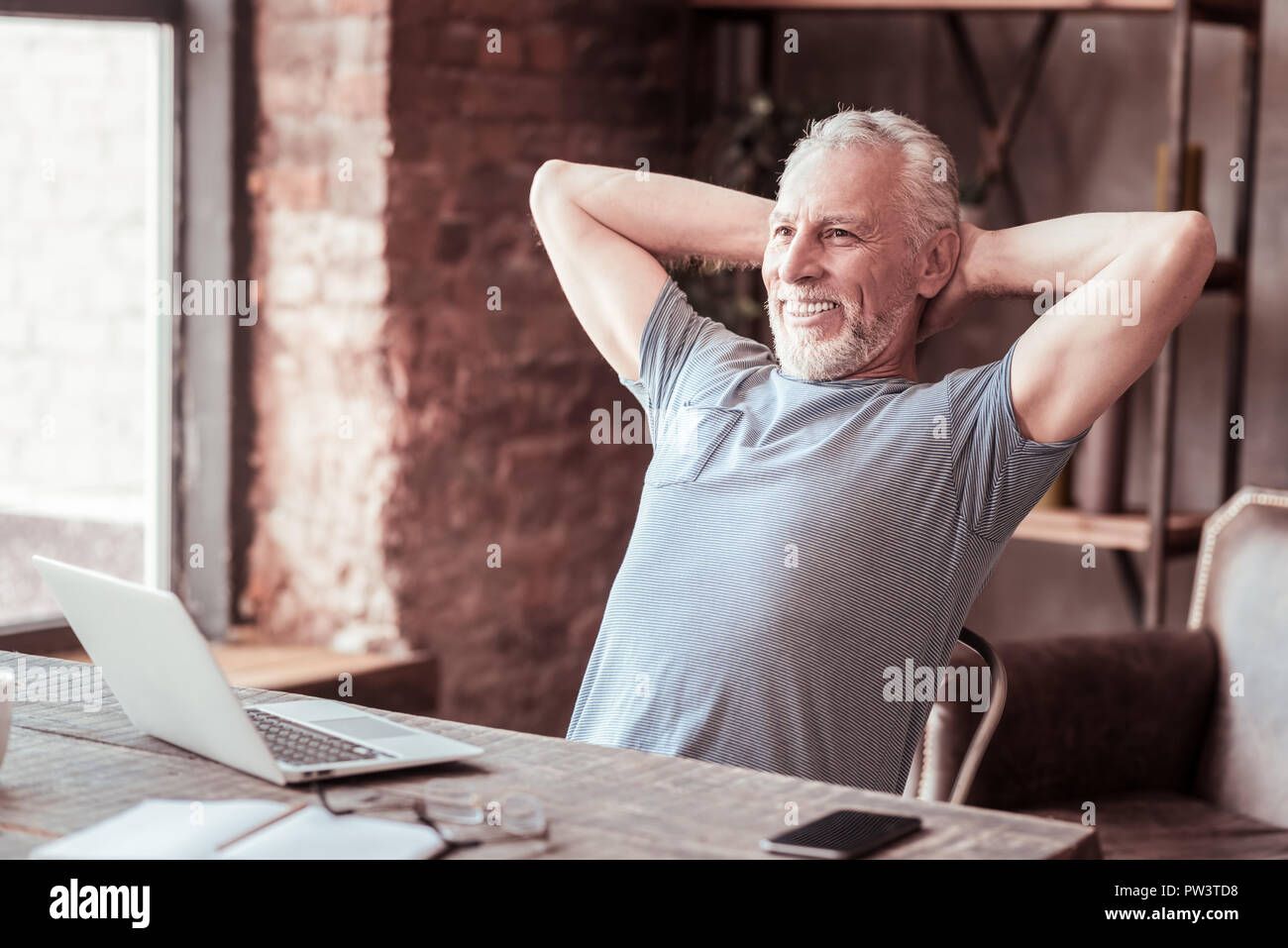 Portrait of relaxed man keeping arms behind his head - Stock Image
