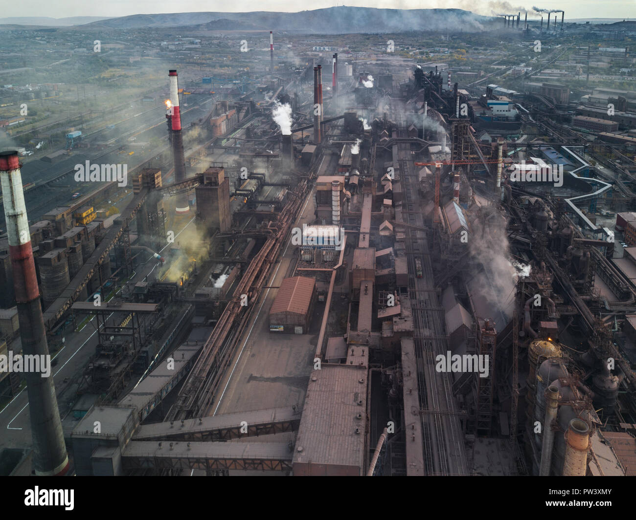 Panoramic view of heavy industry with detrimental impact on nature; CO2 emissions, toxic poisonous gases from chi mneys; rusty dirty pipelines and clo Stock Photo