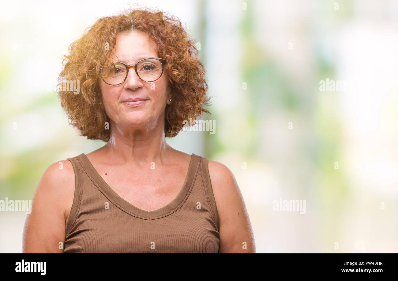 672a8c2cfb1 Middle age hispanic woman wearing glasses over isolated background with  serious expression on face. Simple