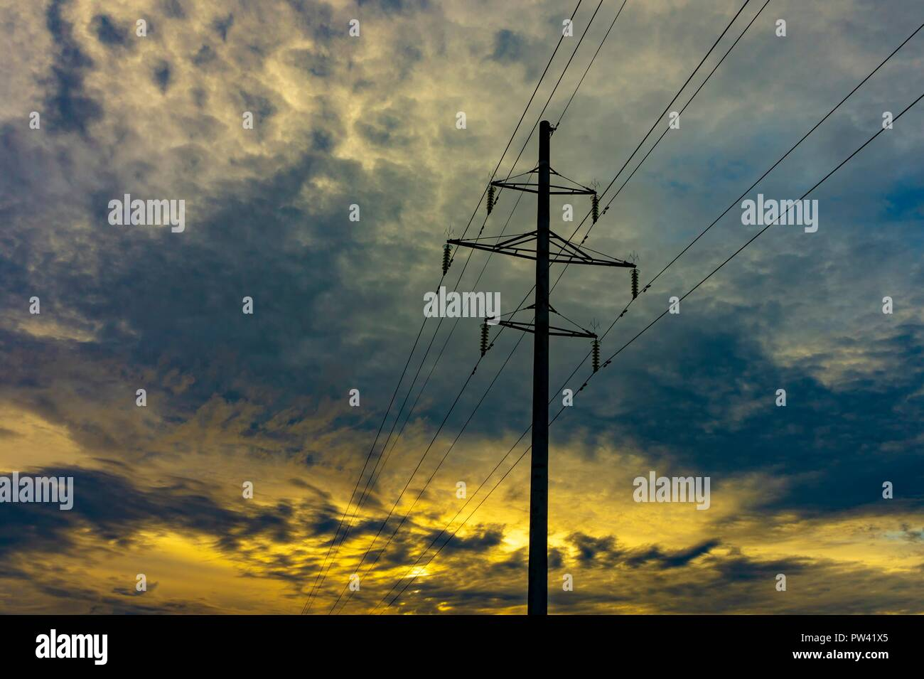 High tension electricity power lines and pole silhouetted against a colorful sunset sky with cloud cover and copy space - Stock Image