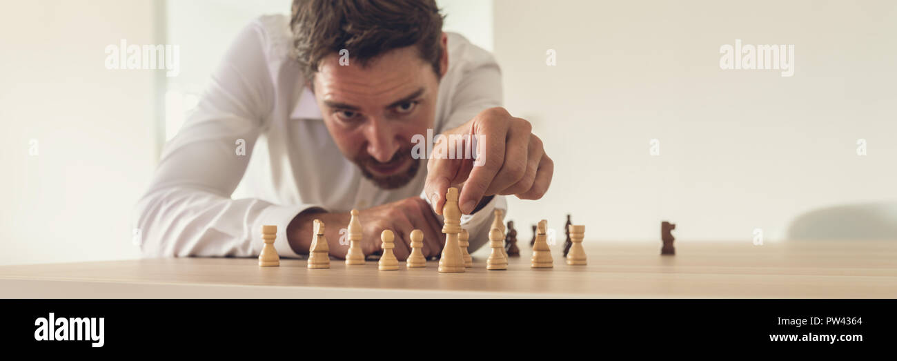 Business executive leaning toward his office desk to precisely place chess figures across the desk with king as the leader. - Stock Image