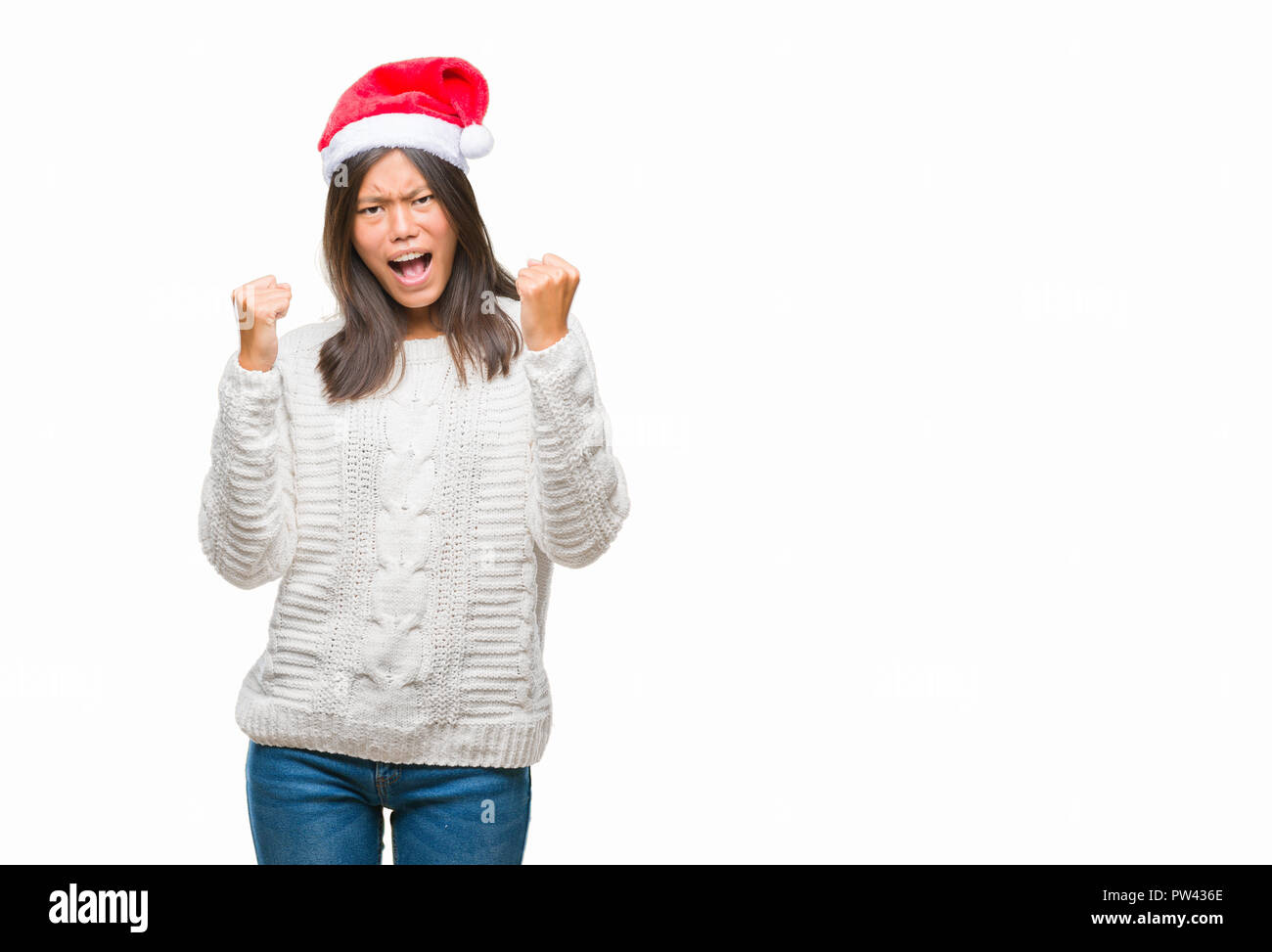 Young asian woman wearing christmas hat over isolated background very happy and excited doing winner gesture with arms raised, smiling and screaming f - Stock Image