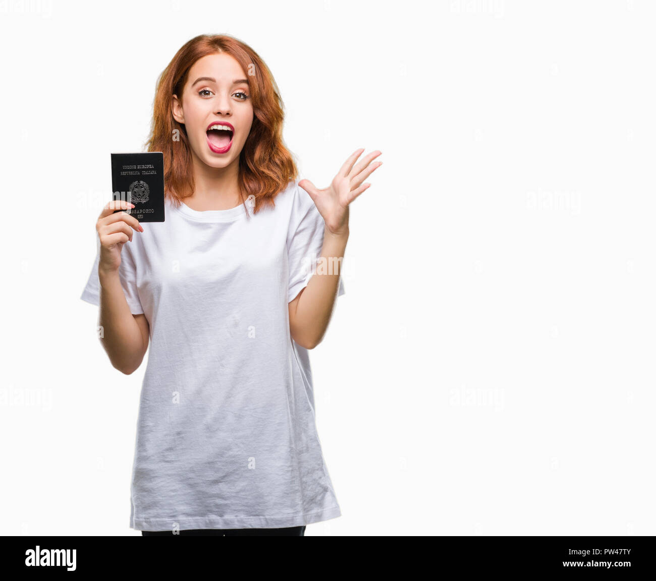 Young beautiful woman holding passport of italy over isolated background very happy and excited, winner expression celebrating victory screaming with  - Stock Image