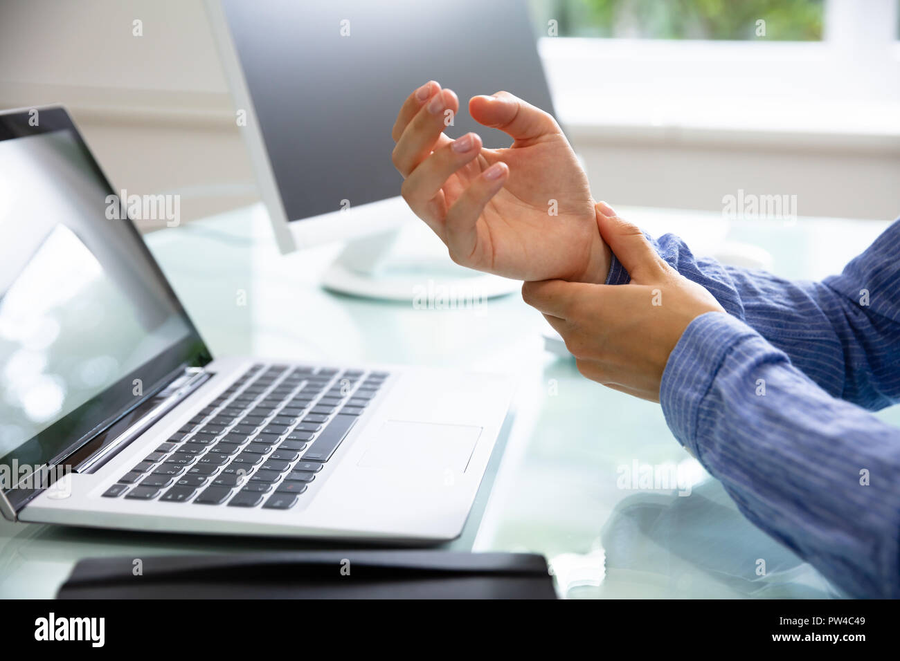 Close-up Of A Businesswoman's Hand Holding Her Painful Wrist With Laptop On Desk - Stock Image