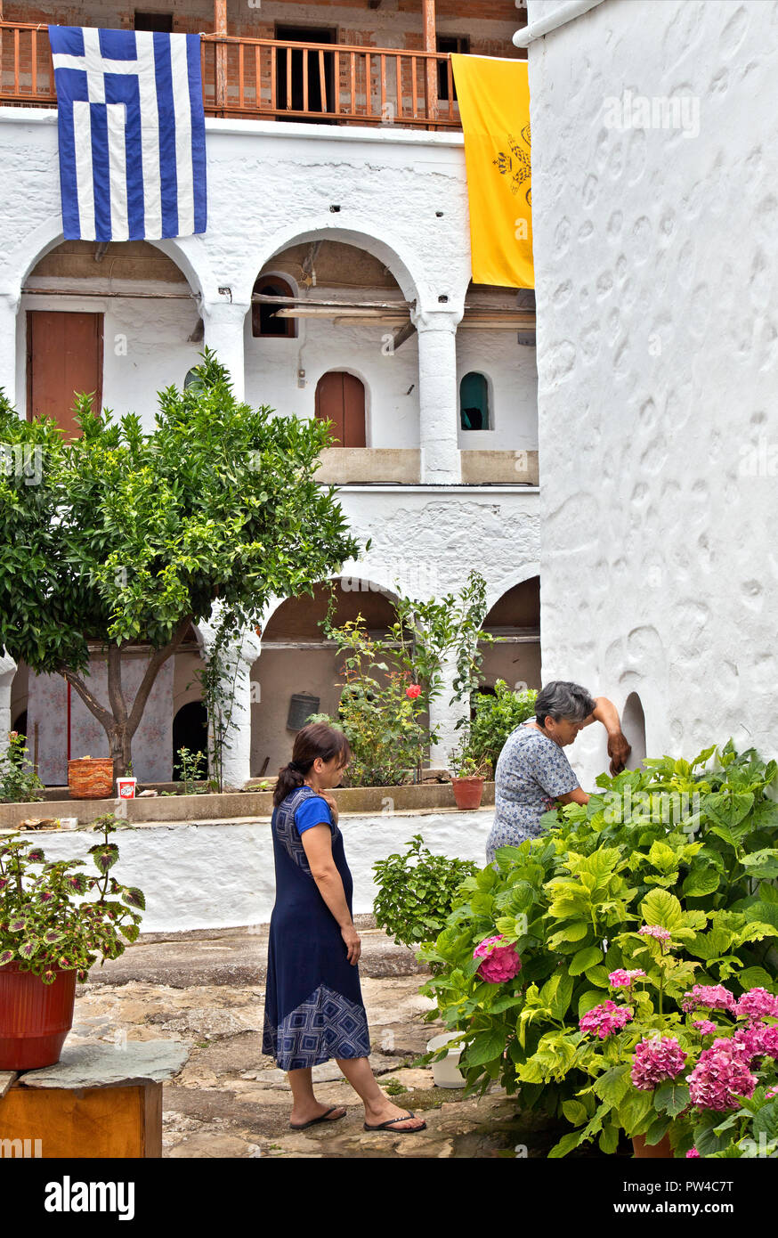 Women cleaning up the courtyard of Timios Prodromos monastery, Palouki mountain, Skopelos island, Northern Sporades, Greece. - Stock Image