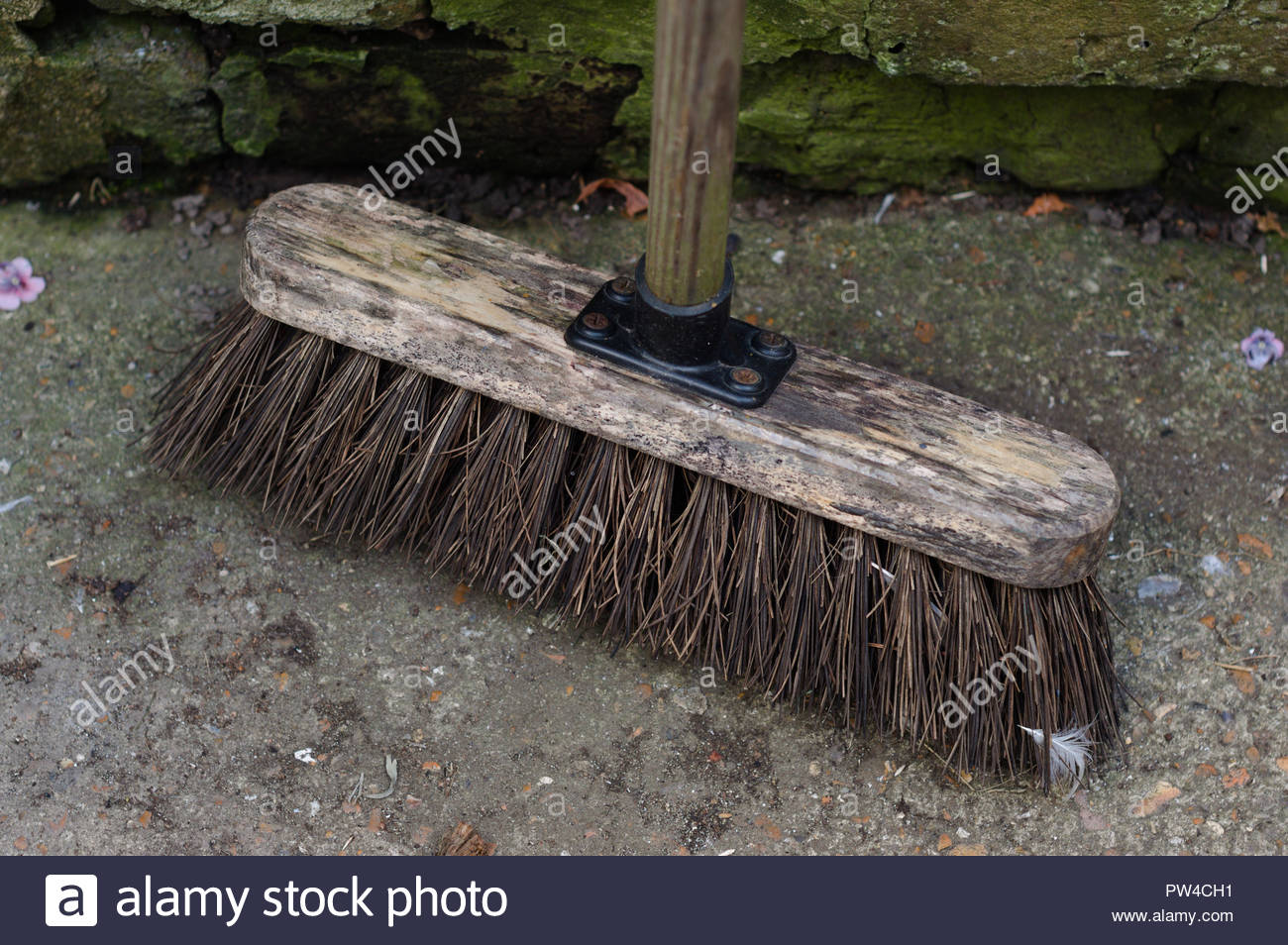 Garden broom standing against stone wall - Stock Image