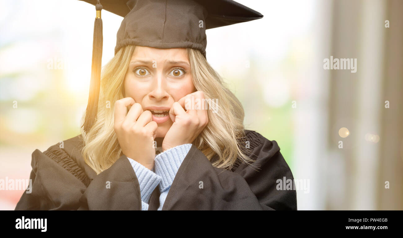 Young graduate woman terrified and nervous expressing anxiety and panic gesture, overwhelmed - Stock Image