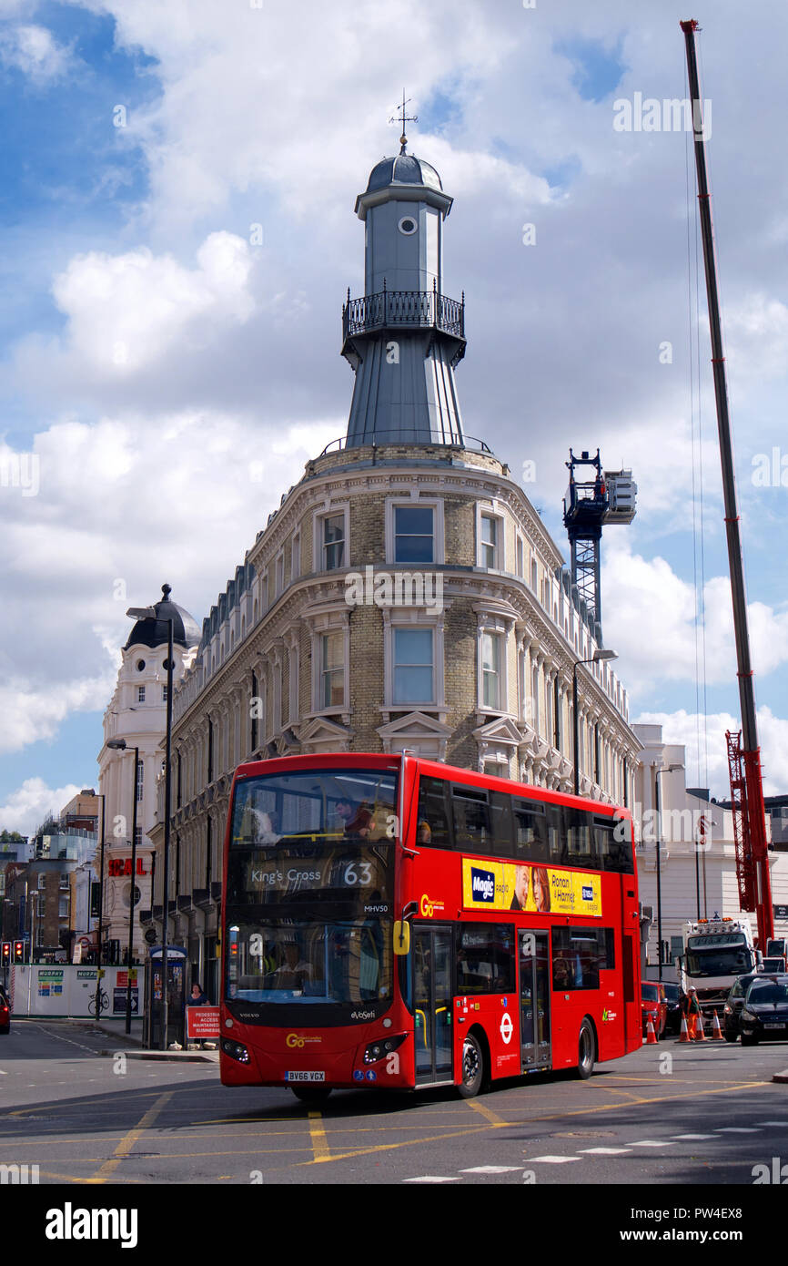 Red Double-Decker Bus in front of the Kings Cross Lighthouse, London - Stock Image