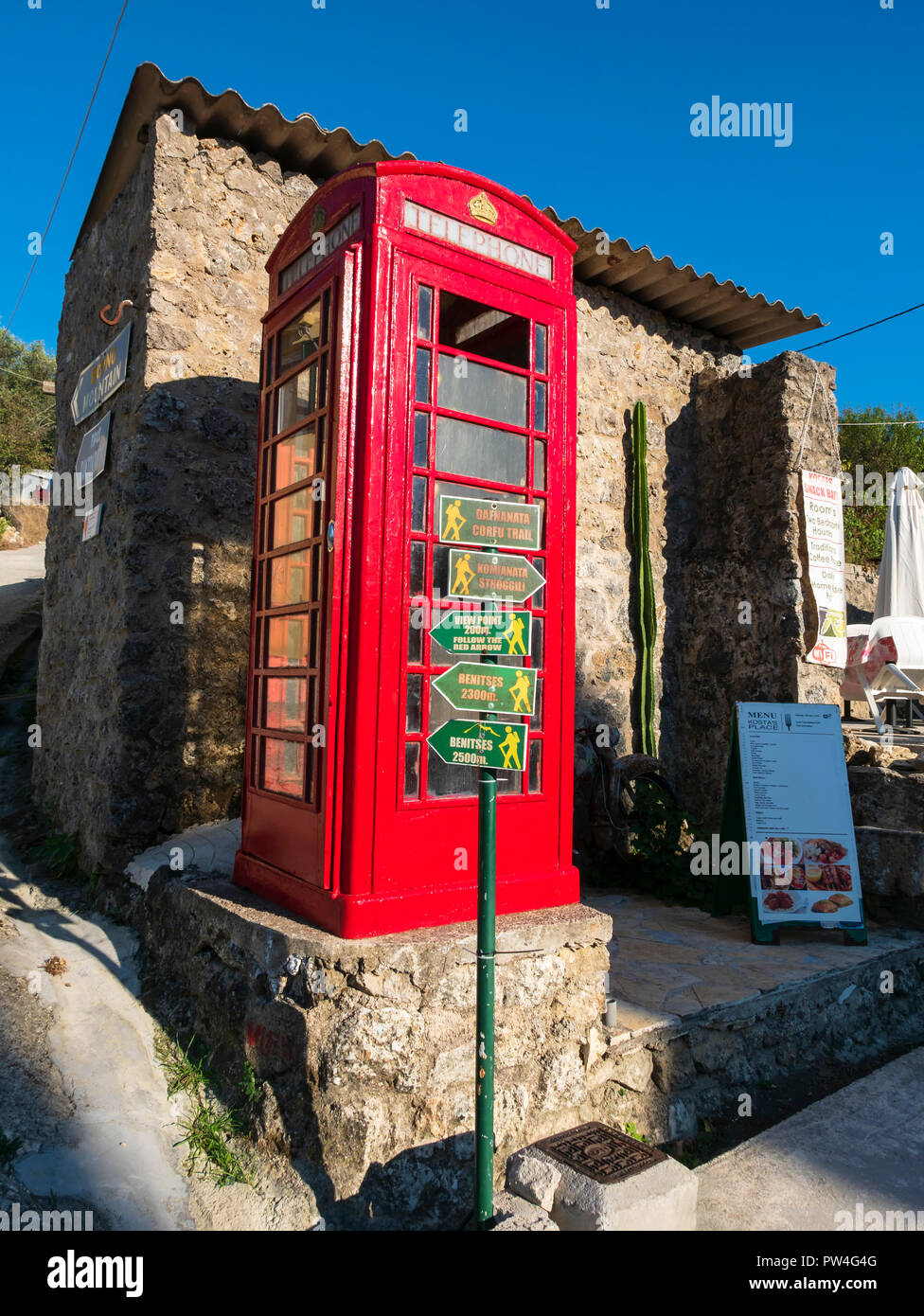 Traditional red British phone box on the Corfu Trail in the village of Dafnata, Corfu, Ionian Islands, Greece. - Stock Image