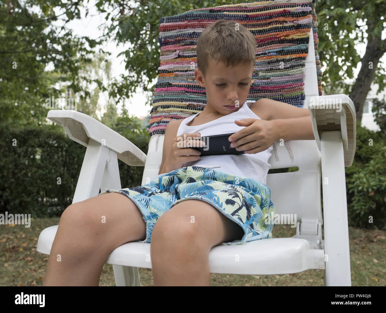 Boy watches a video on his cell phone in the yard in Zielona Gora, Poland. - Stock Image