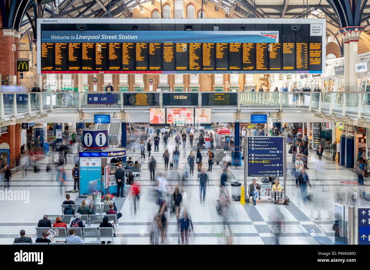 Busy passengers catching their trains at Liverpool Street Station in London. The long exposure captures the moving people as a series of blurs. - Stock Image