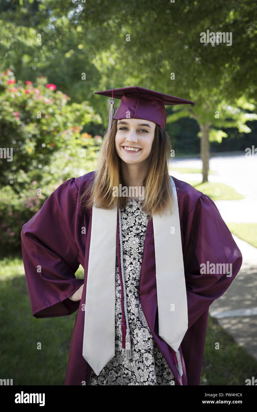 b7bf6944c3 Portrait of happy woman in graduation gown standing against trees at park -  Stock Image