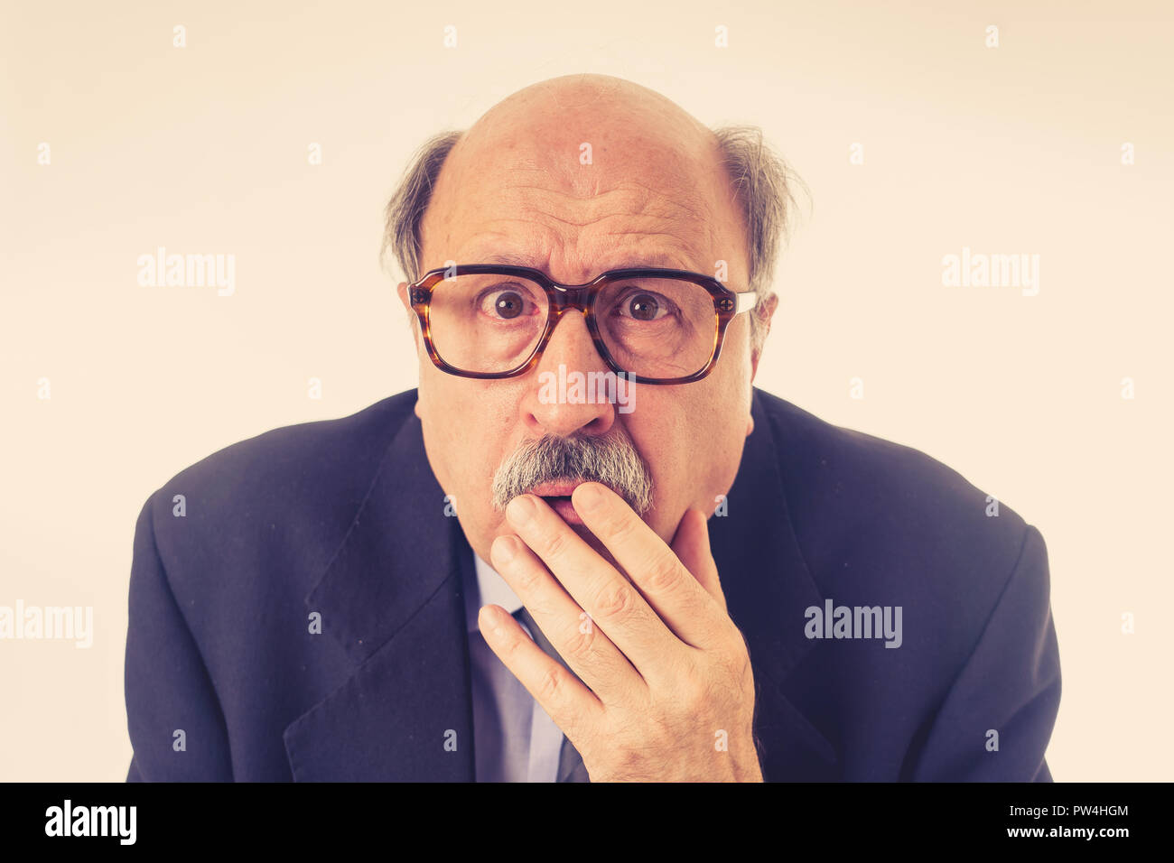 Portrait of a 60s senior man in shock with a scared expression on his face making frightened gestures in human emotions feelings facial expression and - Stock Image