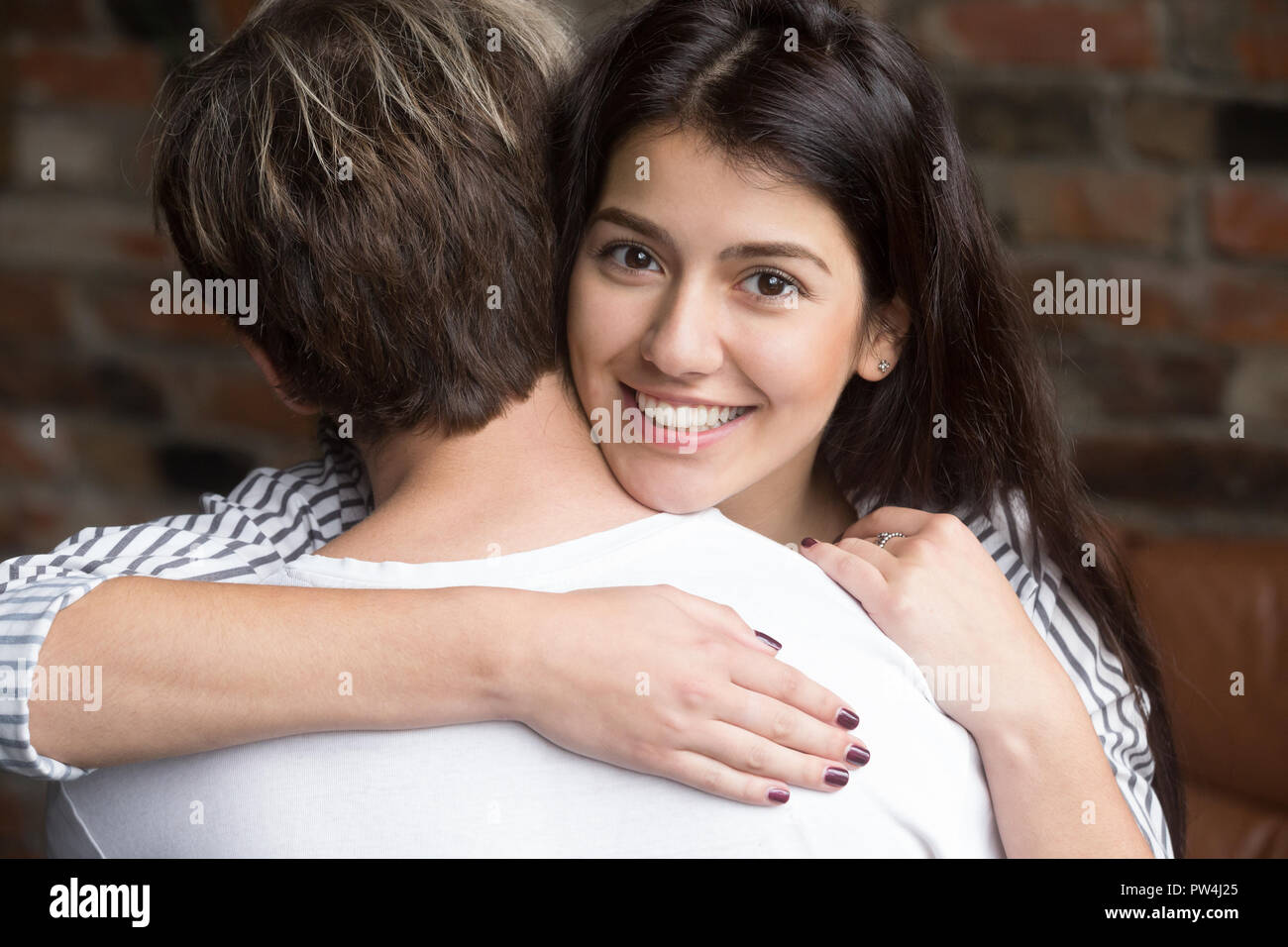 Portrait of young beautiful wife embracing husband - Stock Image