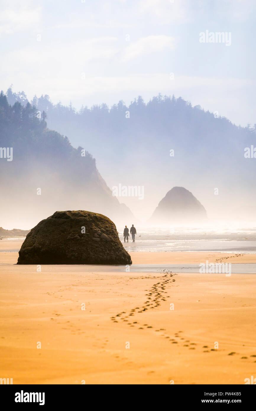 A couple leaves footprints in the sand near Hug Point on the Oregon coast, USA. - Stock Image