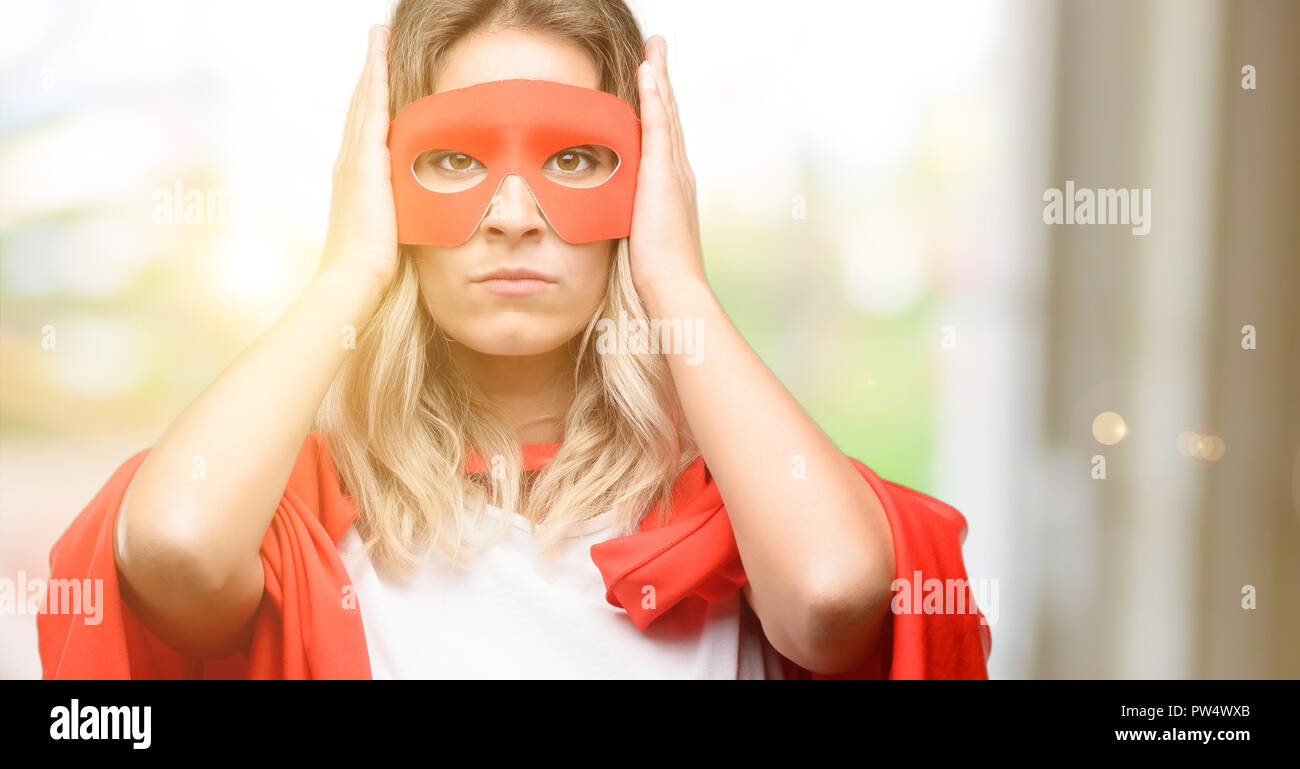 Young super hero woman wearing cape covering ears ignoring annoying