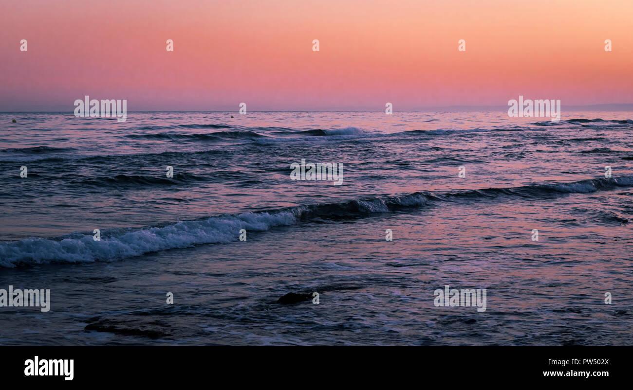 Sunset over Dunas de Artola beach also called Cabopino beach, Marbella, Spain. - Stock Image