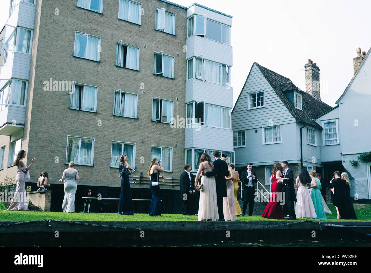 Cambridge students having a graduation party on the grass near the punting river taking group photos - Stock Image