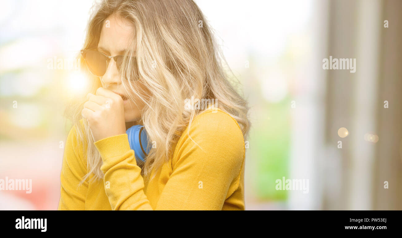 Young beautiful woman with headphones sick and coughing, suffering asthma or bronchitis, medicine concept - Stock Image