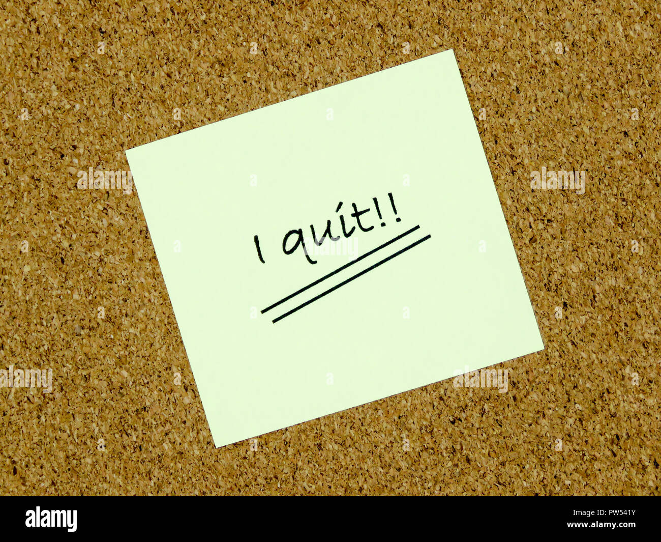 A yellow sticky note with I quit written on it on a cork board background - Stock Image