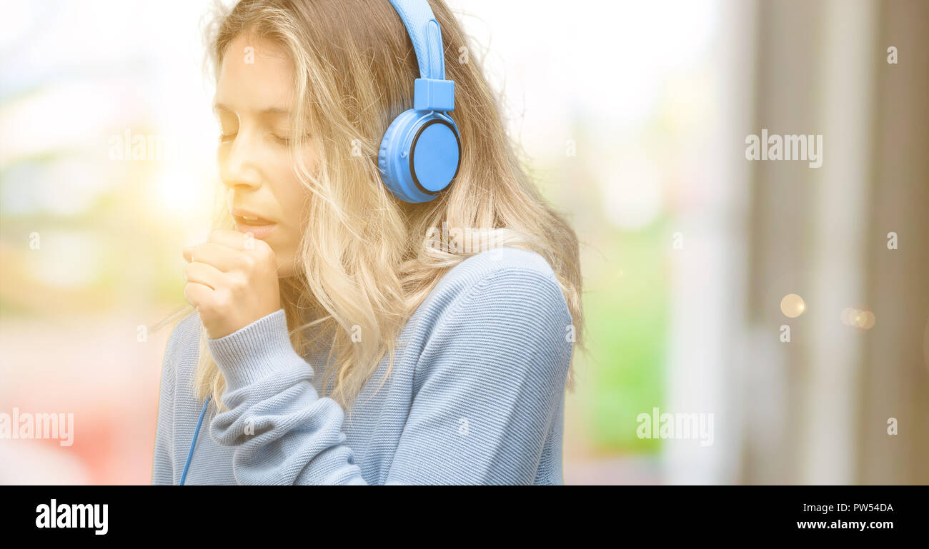 Young beautiful woman listening to music sick and coughing, suffering asthma or bronchitis, medicine concept - Stock Image