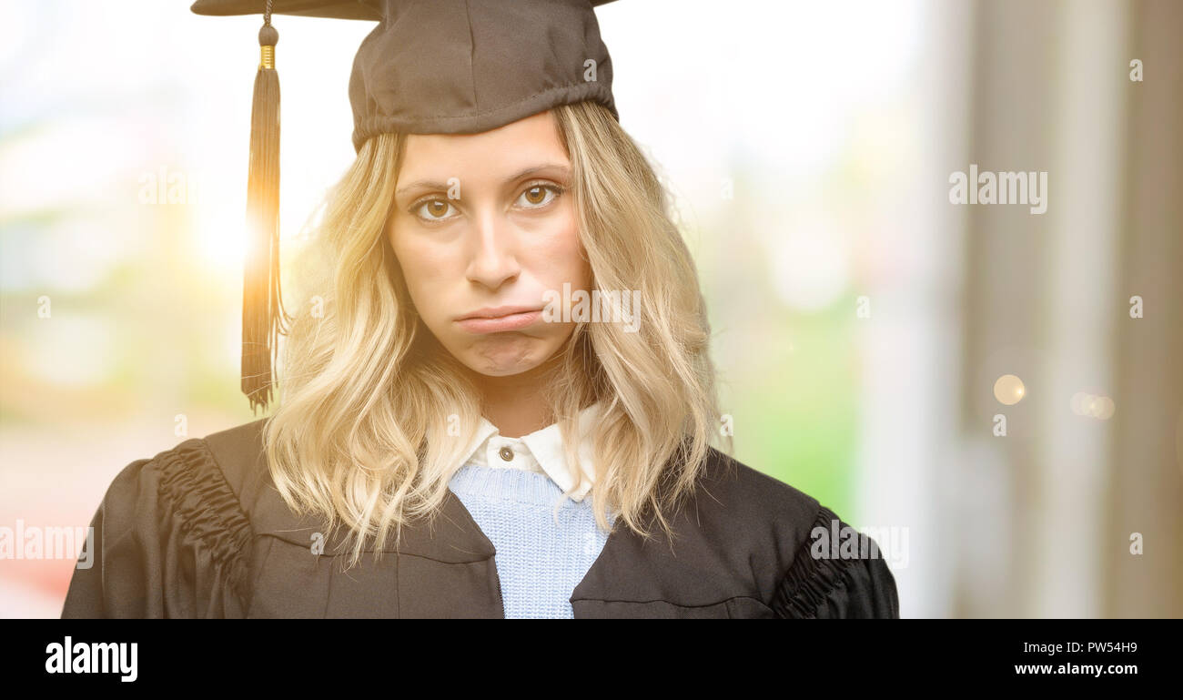 Young graduate woman with sleepy expression, being overworked and tired - Stock Image