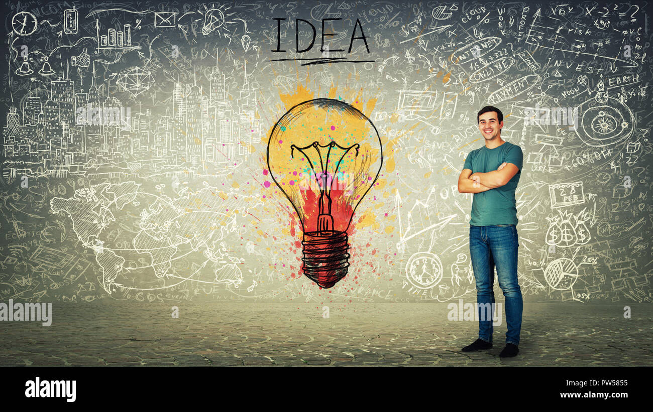 Excited confident young man smiling, hands crossed, colorful light bulb and business sketch on background. Uniqueness of the idea and genius concept. - Stock Image