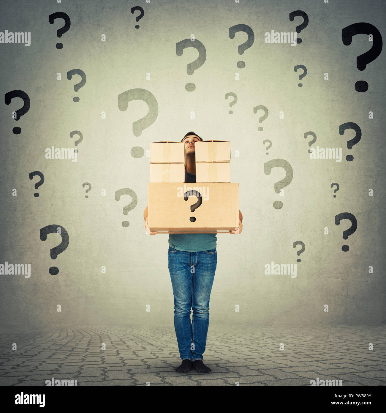 Full length portrait of confused young man carrying heavy packages hidden behind stack of boxes with question marks around. Courier hiding identity of - Stock Image