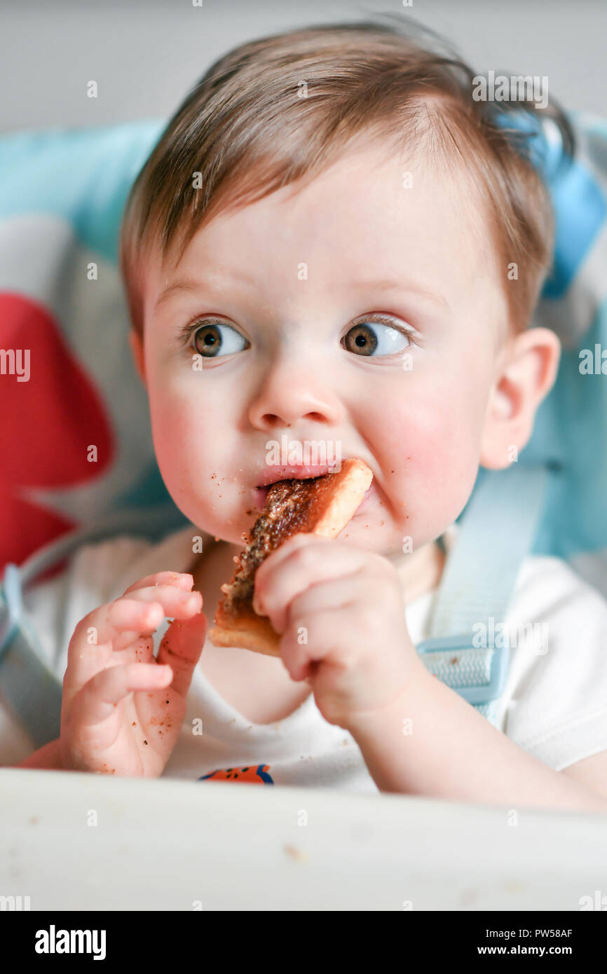 One year old Alexander James eats peanut butter on toast in a high chair - Stock Image