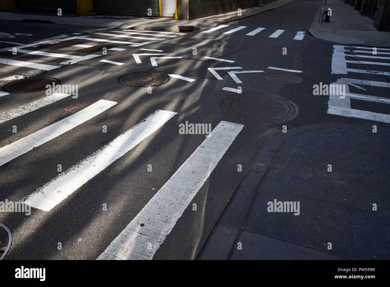 Sunlit intersection with crosswalks and bike lane in New York City - Stock Image