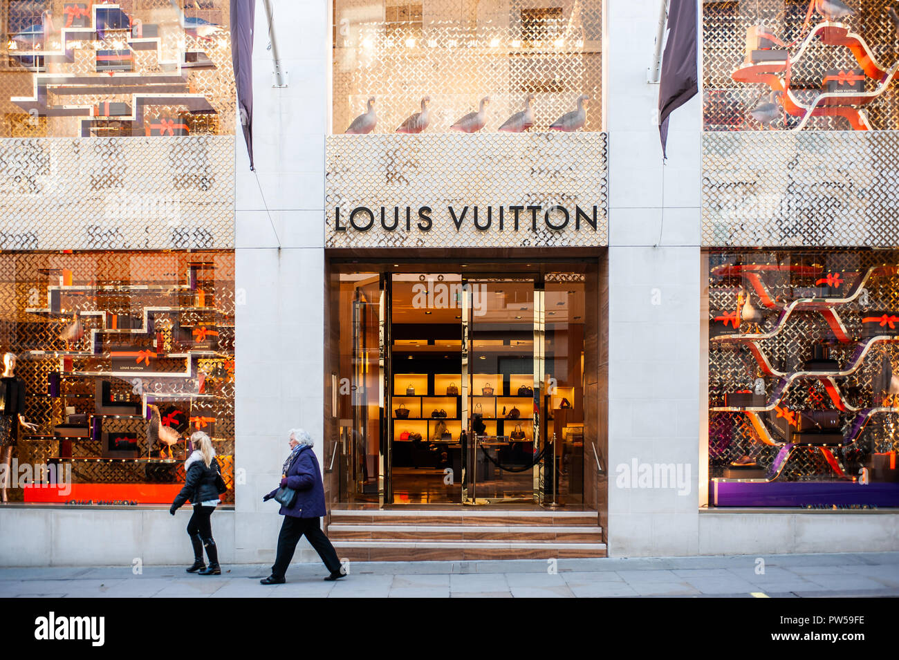 LONDON, UK - NOV 21: People walk in front of the Christmas decorated windows  of the Louis Vuitton boutique in Mayfair, London, UK on November 21, 201 - Stock Image