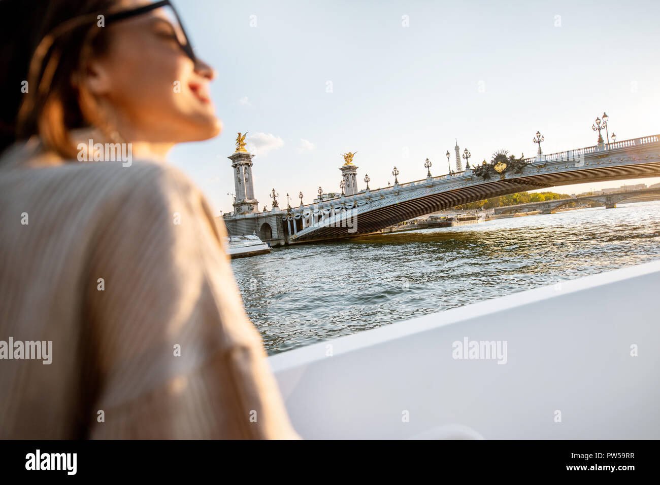 Young woman enjoying beautiful landscape view on the riverside from the ship during the sunset in Paris Stock Photo