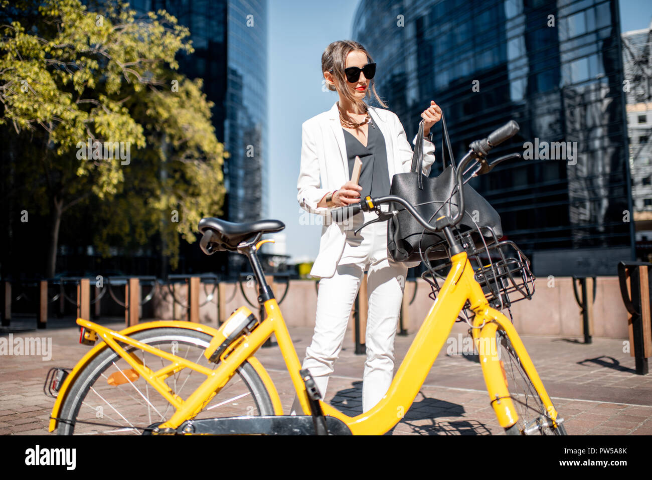 Business woman unlocking public bicycle with smart phone standing at the financial district with skyscrapers on the background Stock Photo