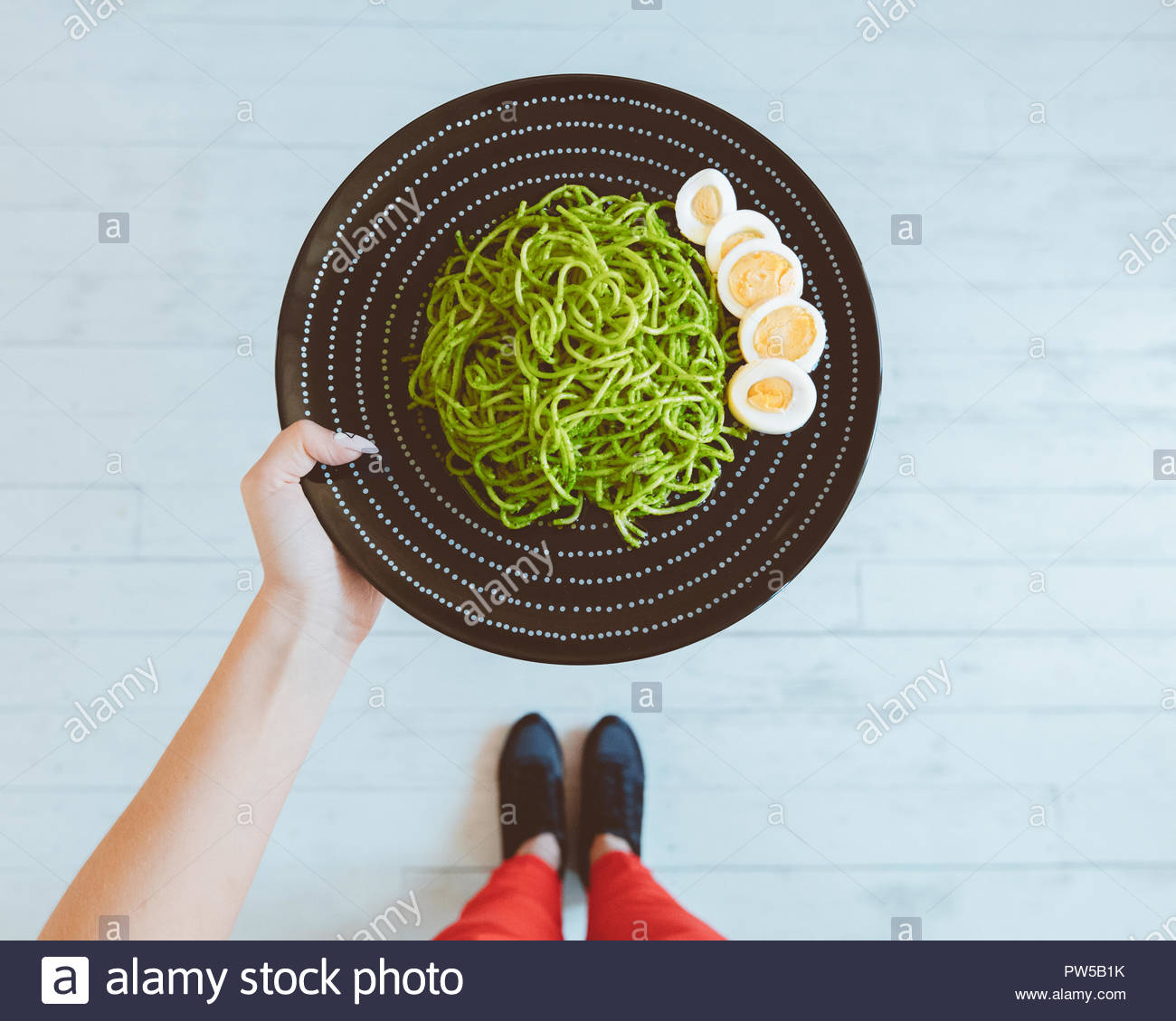 Top view of woman photographing healthy lunch plate aganist floor. Unrecognizable person, close up of meal. - Stock Image