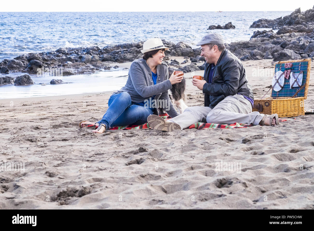 nice middle age caucasian couple happy have fun at the beach doing picnic together in outdoor sea leisure activity. family enjoying love and relations Stock Photo