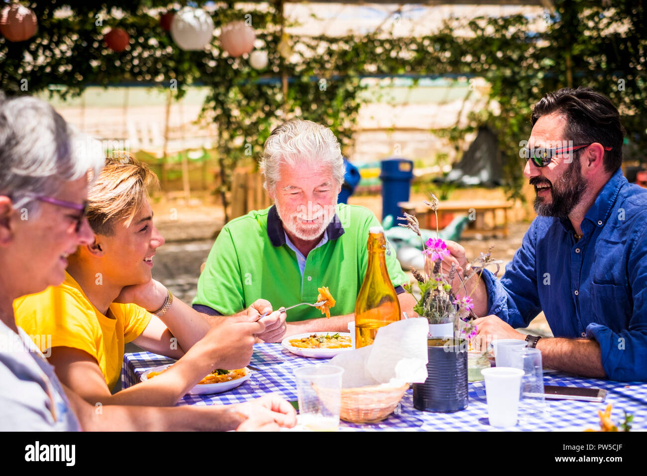 caucasian family having lunch together during a sunny day having fun and smiling while eat italian pasta food. restaurant natural place with cheap dis - Stock Image