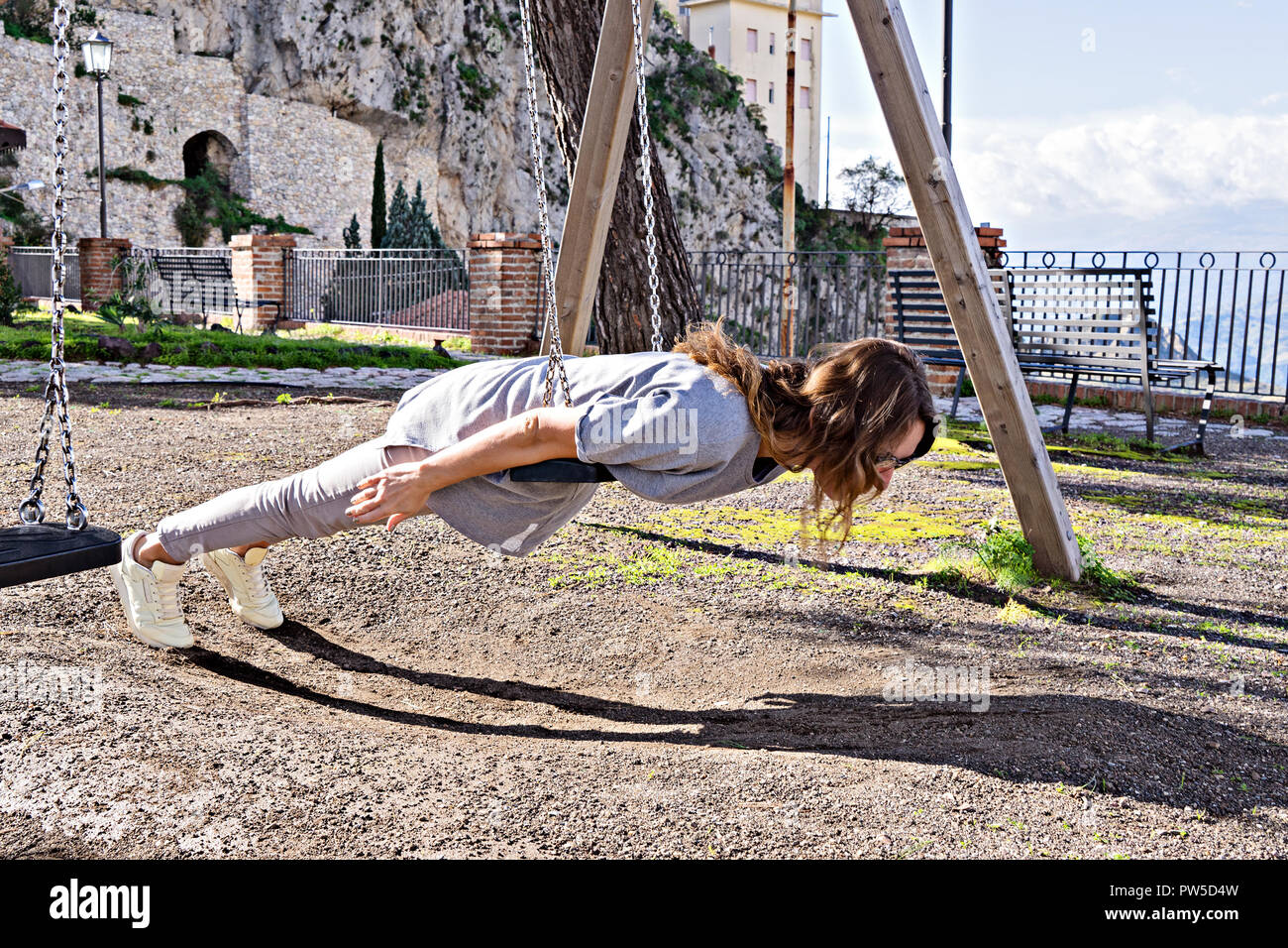 Joyful, beautiful hipster girl in casual look and windy hair, fooling around on swing planking, deadpan style photo, instagram effect - Stock Image