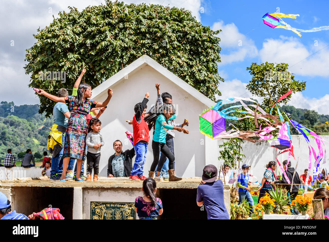 Santiago Sacatepequez, Guatemala - November 1, 2017: Flying kites honoring spirits of the dead in cemetery on All Saints Day. - Stock Image