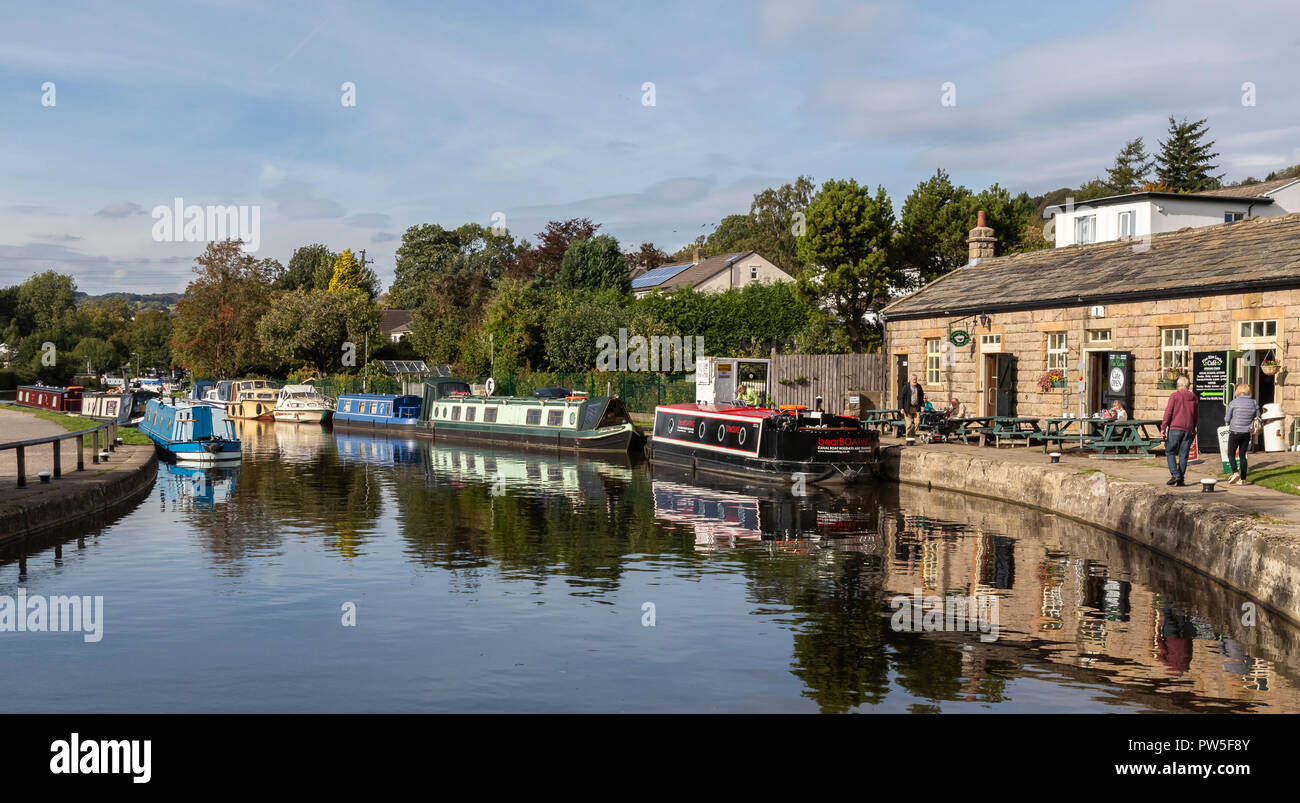 Barges on the Leeds Liverpool Canal at the top of the Five Rise Locks at Bingley, West Yorkshire. Five Rise Locks cafe is on the waters edge. - Stock Image