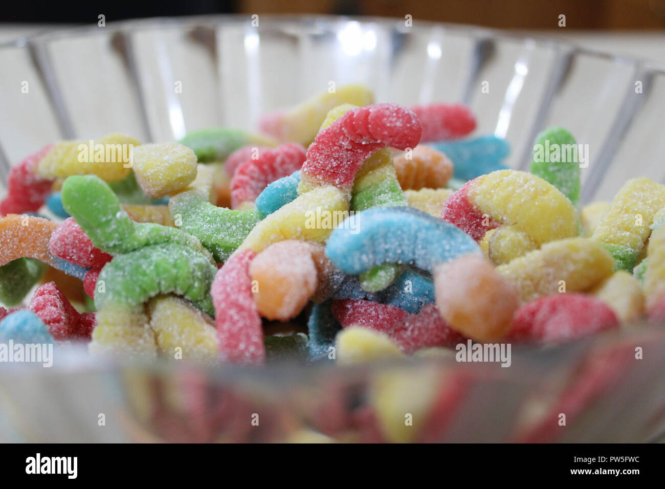 Close-up of gummy worms in plastic serving bowl - Stock Image