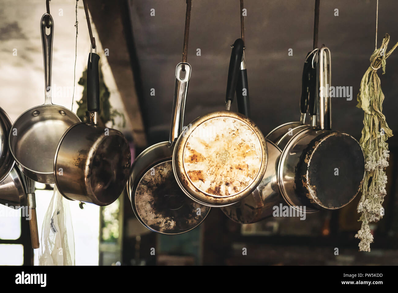 Pots and pans hanging on hooks in a farm kitchen Stock Photo ...