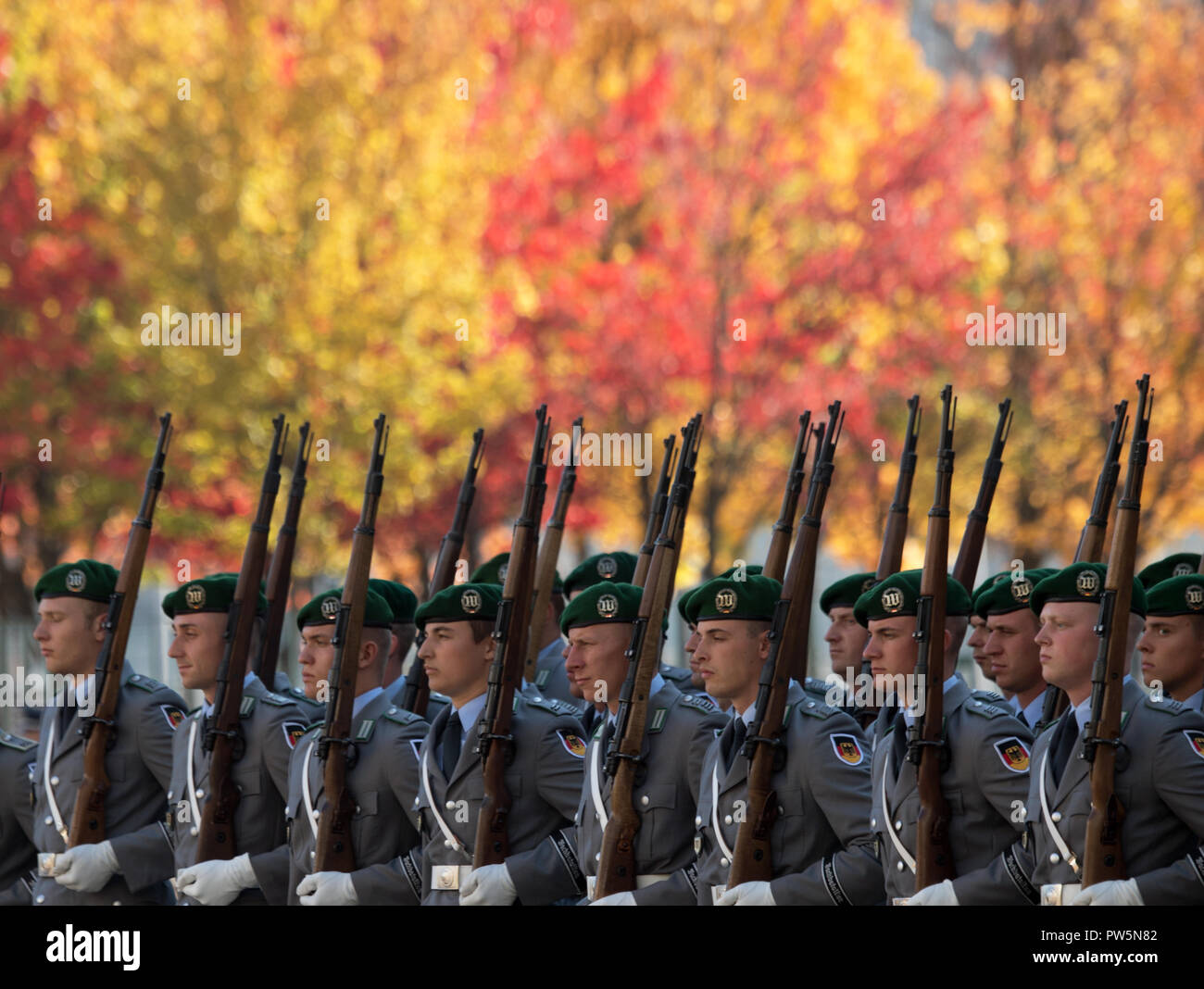 12 October 2018, Berlin: 12October 2018, Germany, Berlin:Soldiers of the guard battalion of the German Armed Forces have entered the reception of the Slovenian Prime Minister Sarec with military honours in the protocol courtyard of the Chancellery, in the background the foliage of trees shines in autumnal colours. Photo: Ralf Hirschberger/dpa - Stock Image