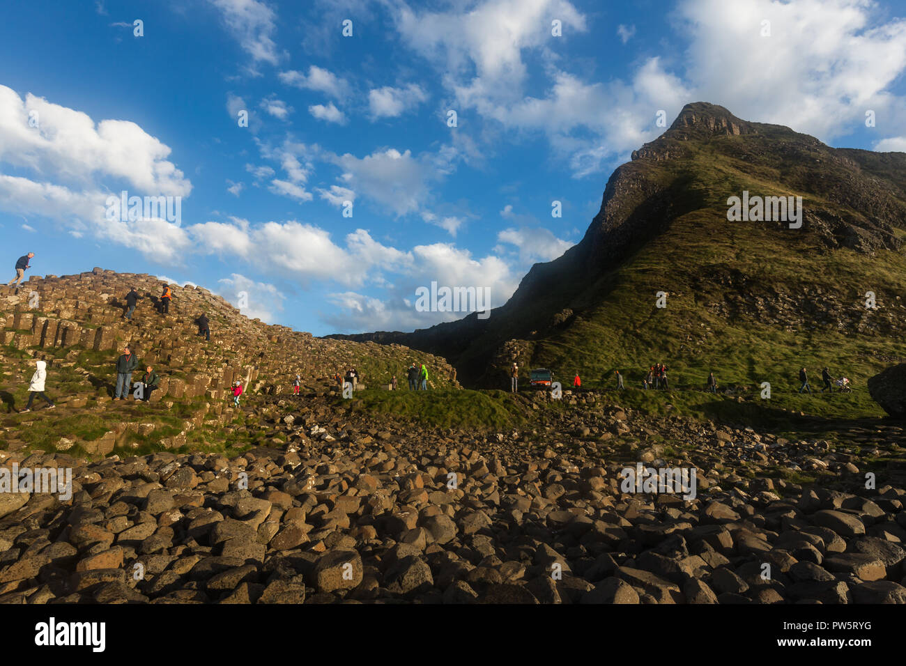 Giants Causeway, County Antrim, N.Ireland, 12th October, 2018. UK Weather: Bright sunny afternoon with strong gusts following strong winds and grey skies from Storm Callum in the morning. Tourists enjoy wonderful bright conditions at Northern Ireland's top attraction, with thousands of basalt hexagonal columns. Credit: Ian Proctor/Alamy Live News - Stock Image