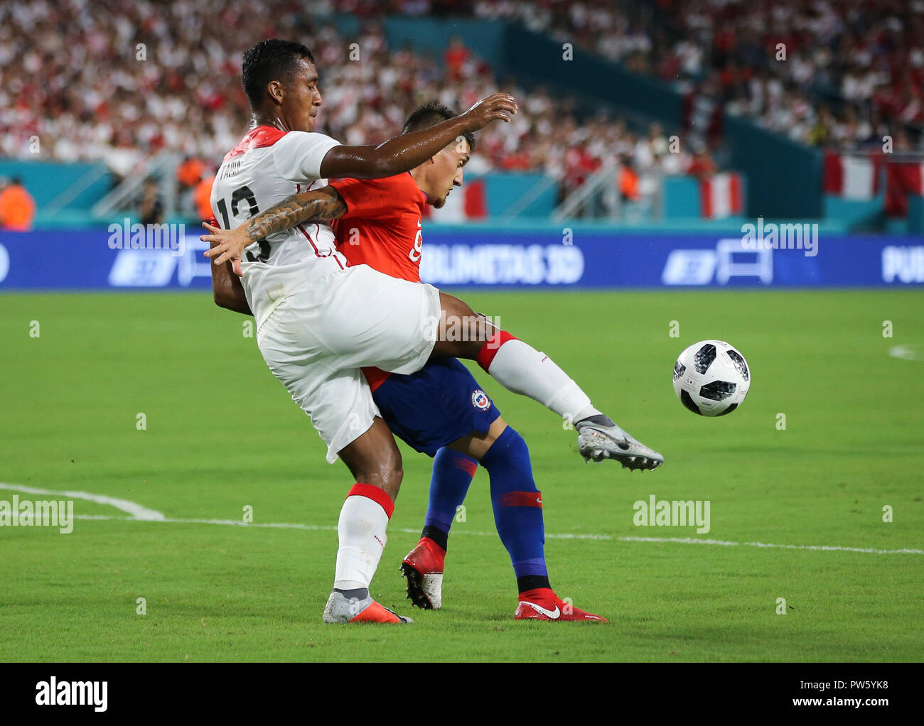 Miami Gardens, Florida, USA. 12th Oct, 2018. Peru midfielder RENATO TAPIA (13) battles for ball possession with Chile forward NICOLAS CASTILLO (9) during an international friendly match between the Peru and Chile national soccer teams, at the Hard Rock Stadium in Miami Gardens, Florida. Credit: Mario Houben/ZUMA Wire/Alamy Live News - Stock Image