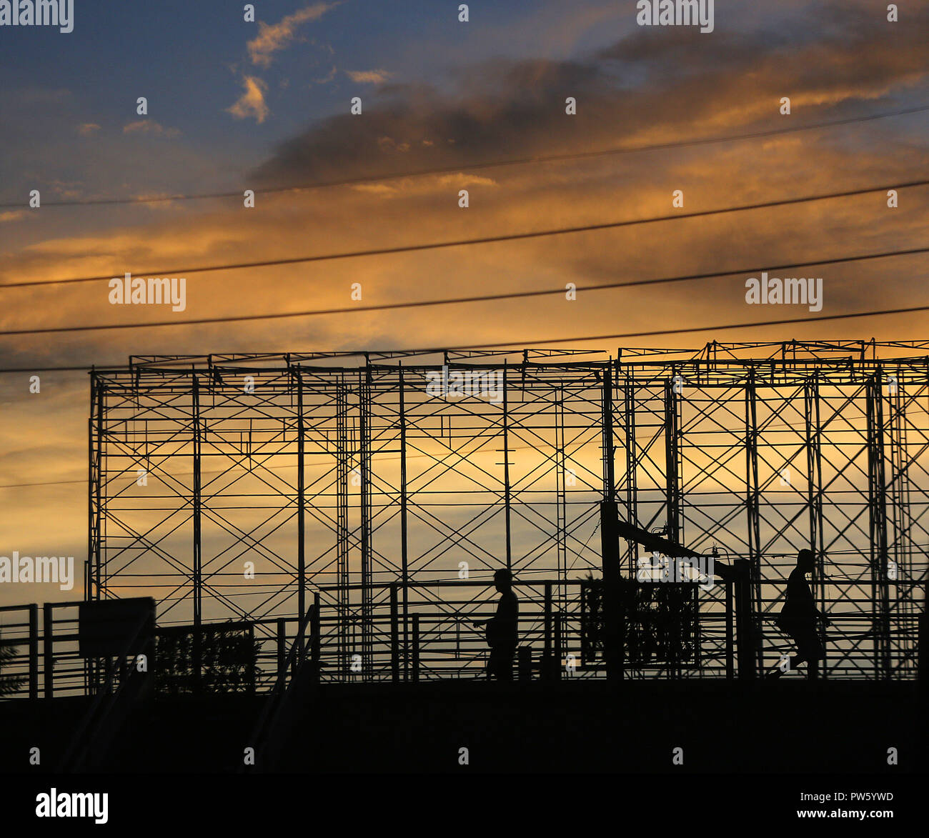 Pasay City, Philippines. 13th Oct, 2018. People are silhouetted against the sky during sunrise in Pasay City, Philippines, Oct. 13, 2018. Credit: Rouelle Umali/Xinhua/Alamy Live News - Stock Image
