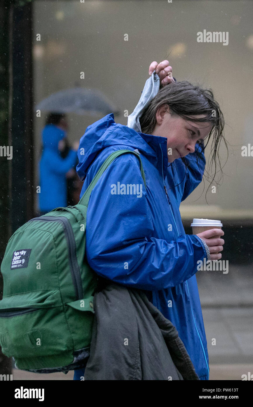 Southport, Merseyside. UK Weather. Strong winds and heavy rain in the north-west resort town centre. Woman, carrying knapsack, bags with wet hair adjusting hood after downpour. Credit; MediaWorldImages/AlamyLiveNews. - Stock Image