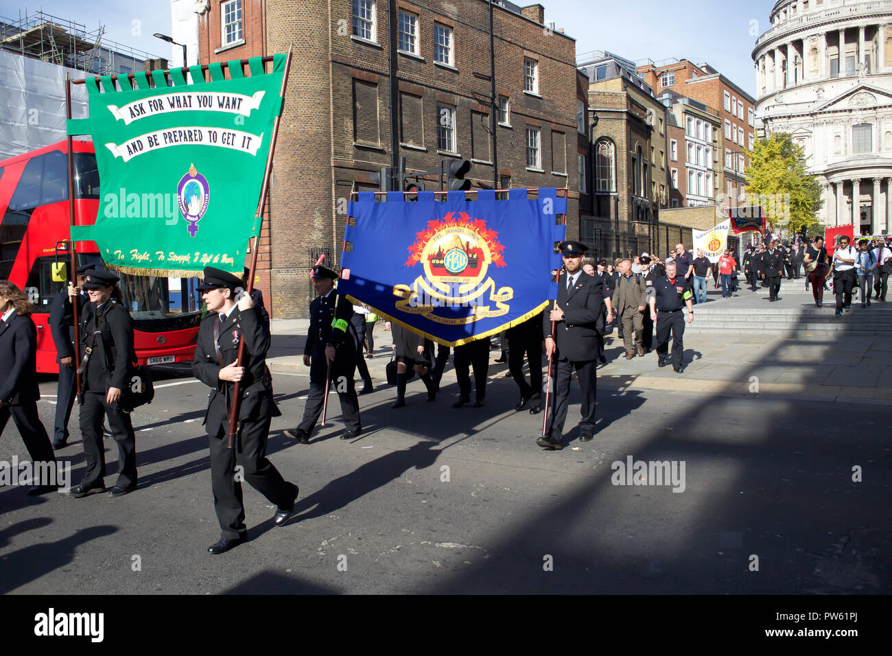 London,UK,13th October 2018,As part of celebrations to mark 100 years since the Fire Brigades Union (FBU) was formed, a formal wreath-laying ceremony took place at the National Firefighters' Memorial at St Paul's Cathedral in London. More than 50 wreaths were laid in memory of fallen firefighters representing every fire service in the UK. Following this ceremony, a formal procession walked across the Millennium Bridge to Southwark Cathedral where a service took place including readings, poetry, storytelling and music to celebrate 100 years of the FBU.Credit Keith Larby/Alamy Live News - Stock Image