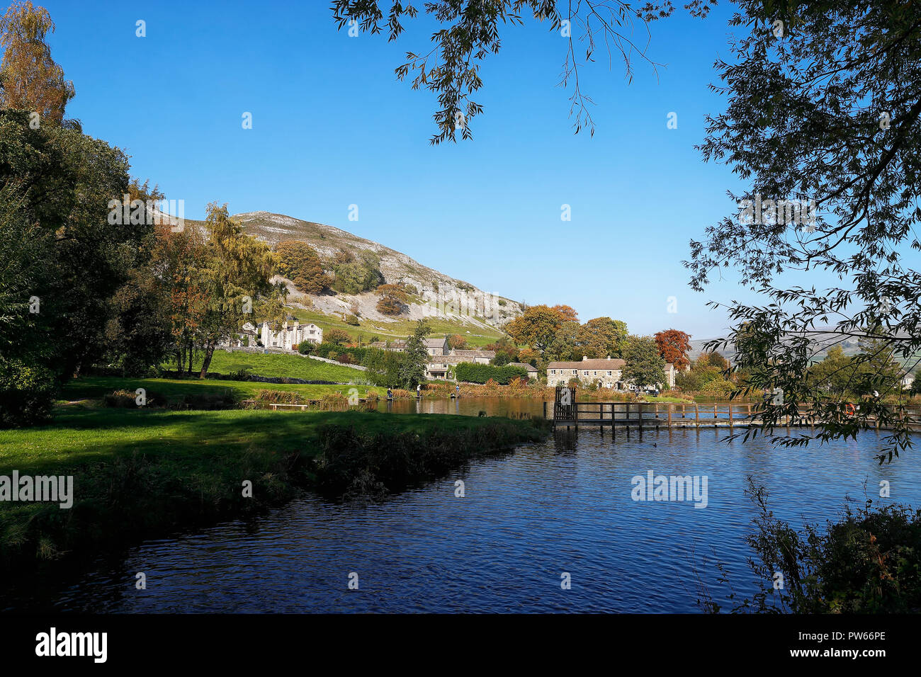 Kilnsey Trout farm fishing lakes with the village in the background with the Crag rising above Stock Photo