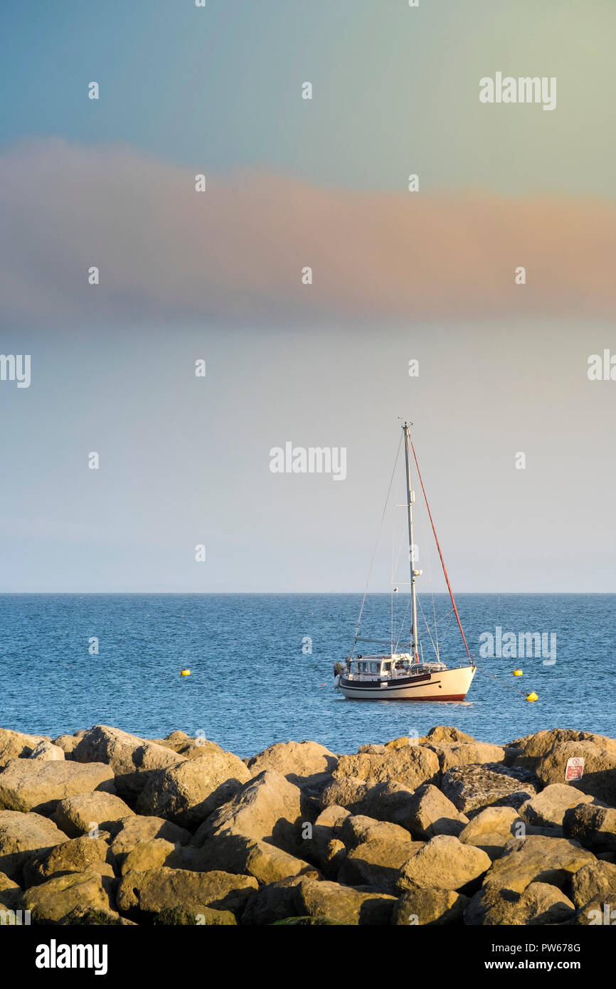 A sail boat moored in the sea off the coast of Lyme Regis in Dorset. - Stock Image