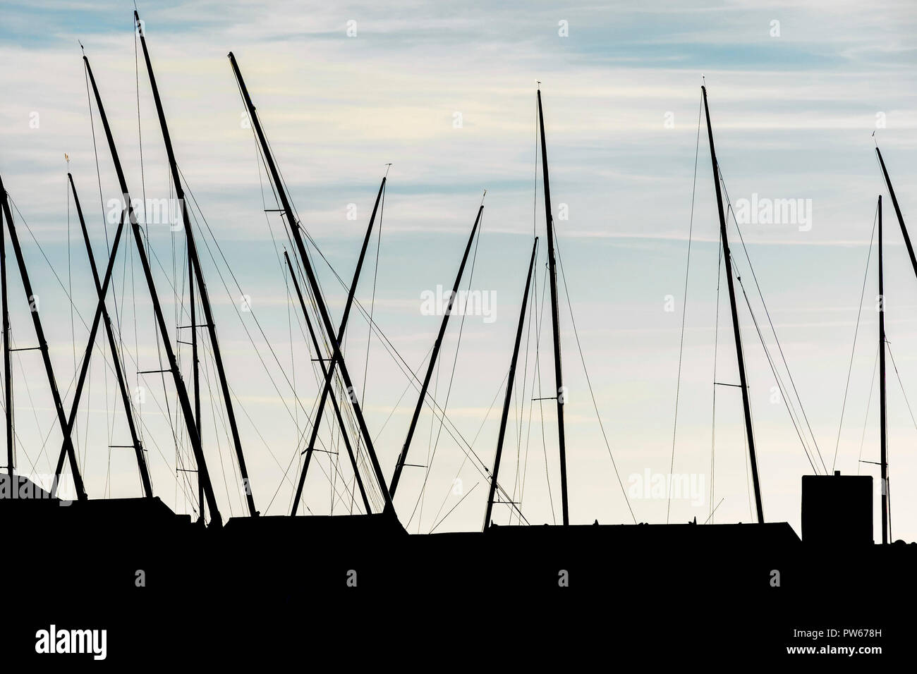 The masts of sail boats seen in silhouette. - Stock Image